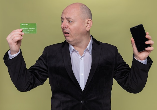 Middle-aged bald man in suit holding smartphone and credit card looking at it confused and very anxious standing over green wall