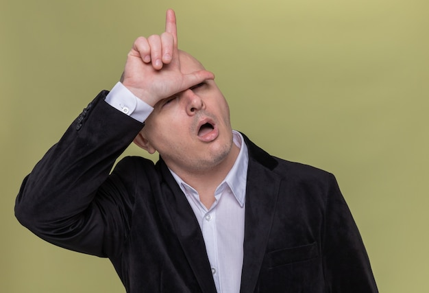 Middle-aged bald man in suit making loser gesture with fingers over his head standing over green