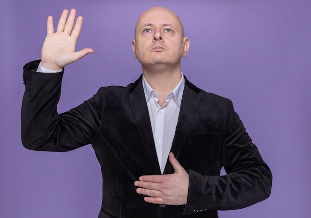 Uomo calvo di mezza età in vestito che fa una promessa tenendo la mano sul petto e alzando l'altra mano in piedi sul muro viola