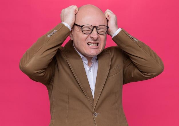 Uomo calvo di mezza età in vestito con gli occhiali che urlano pugni serrati selvaggi