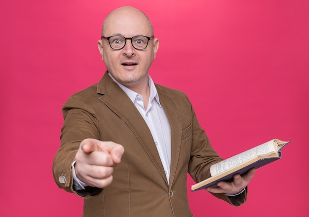 Uomo calvo di mezza età in vestito con gli occhiali che tiene il libro guardando davanti sorpreso che punta con il dito indice alla telecamera in piedi sopra il muro rosa