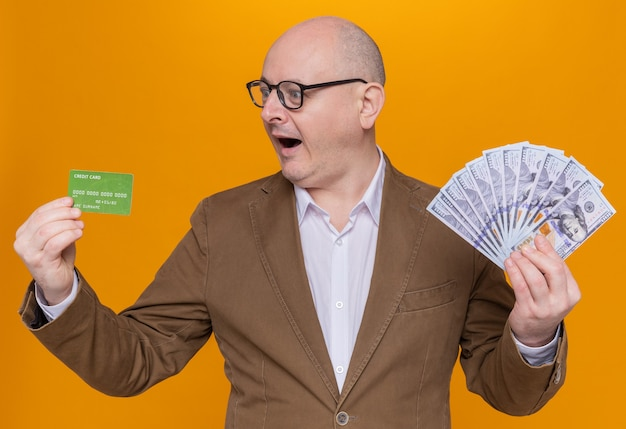 Middle-aged bald man in suit wearing glasses holding cash and credit card looking at it happy and excited smiling cheerfully standing over orange wall