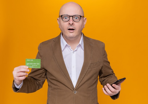 Middle-aged bald man in suit wearing glasses holding credit card and mobile phone looking at front amazed and surprised standing over orange wall