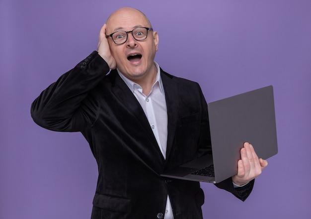 Uomo calvo di mezza età in vestito con gli occhiali che tiene il computer portatile che osserva da parte confuso con la mano sulla sua testa per errore in piedi sopra il muro viola