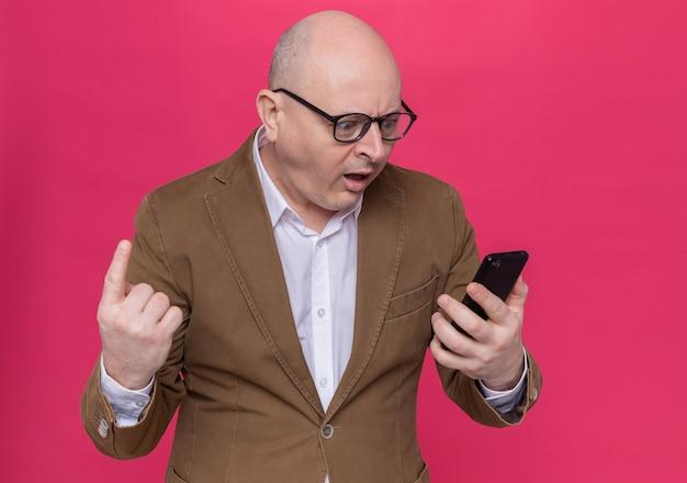 Uomo calvo di mezza età in vestito con gli occhiali che tiene il telefono cellulare guardandolo stupito e sorpreso mostrando il dito indice in piedi sul muro rosa