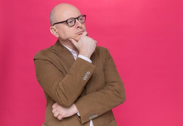 Uomo calvo di mezza età in vestito con gli occhiali che osserva da parte con la mano sul mento pensando con espressione pensierosa in piedi sul muro rosa