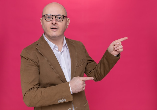 Uomo calvo di mezza età in vestito con gli occhiali che guarda l'obbiettivo felice e sorpreso che punta