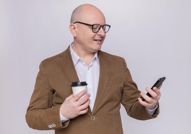 Uomo calvo di mezza età in vestito con gli occhiali guardando lo schermo del suo telefono cellulare che tiene la tazza di carta sorridente fiducioso in piedi sopra il muro bianco