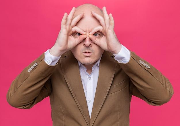 Uomo calvo di mezza età in vestito con gli occhiali guardando attraverso le dita