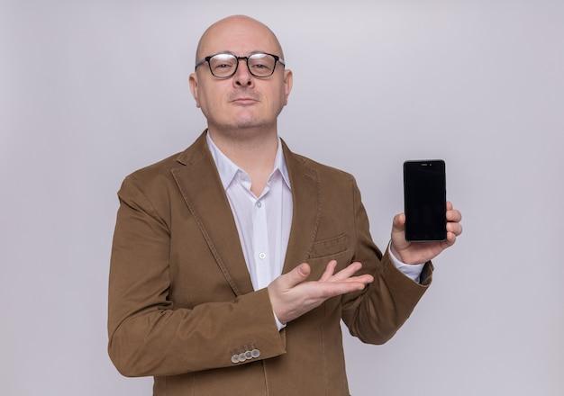 Uomo calvo di mezza età in vestito con gli occhiali che presenta smartphone guardando davanti sorridente fiducioso in piedi sopra il muro bianco
