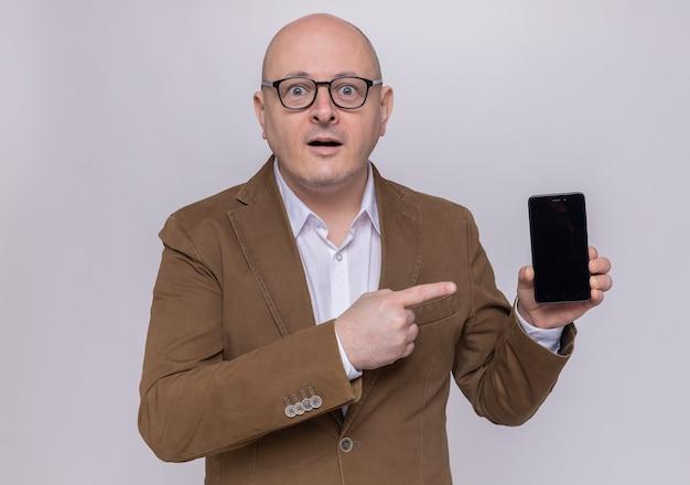 Uomo calvo di mezza età in vestito con gli occhiali che presenta puntamento dello smartphone