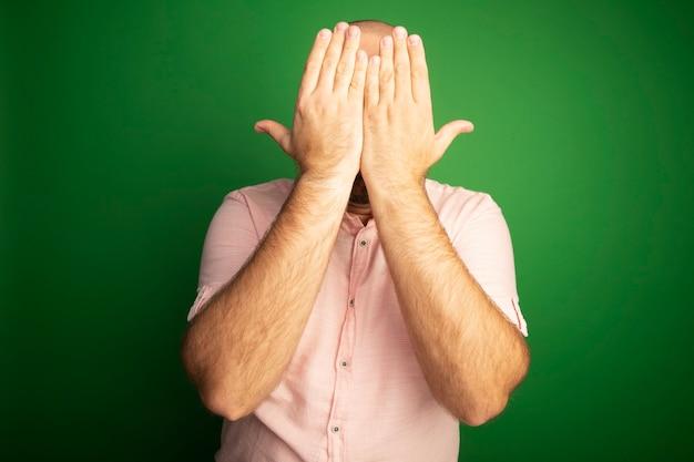 緑の壁に隔離された手でピンクのtシャツで覆われた顔を身に着けている中年のハゲ男