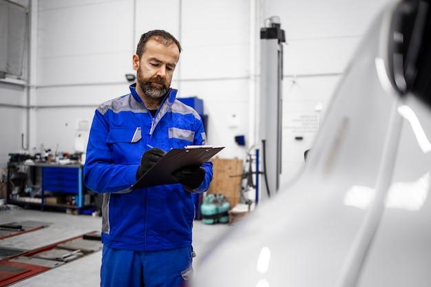 ワークショップで車両の目視検査を行い、チェックリストを保持している中年のひげを生やした白人の自動車整備士。