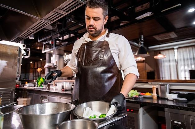 エプロンと手袋をはめた中年のひげを生やしたシェフがストーブに立って、レストランのキッチンで鍋から調理されたブロッコリーを取り出します