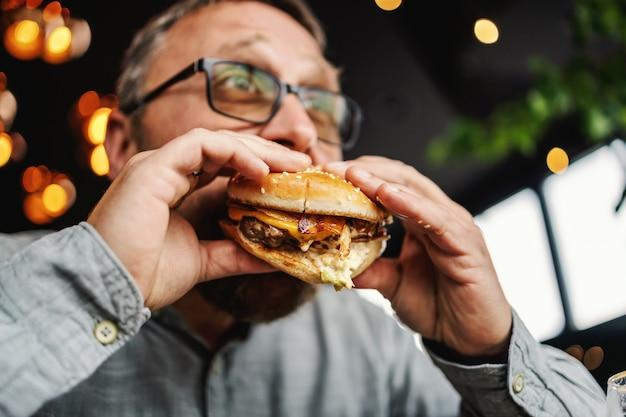 レストランに座っておいしいハンバーガーを食べている中年のひげを生やした空腹の男。