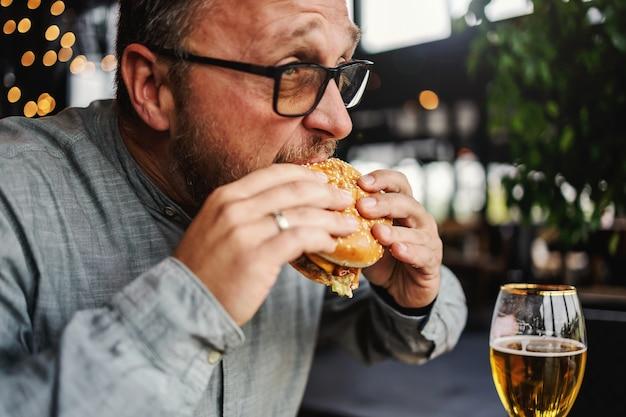 Бородатый голодный мужчина средних лет сидит в ресторане и ест вкусный гамбургер