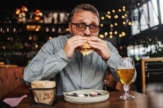 Middle aged bearded hungry man sitting in restaurant and eating delicious burger.