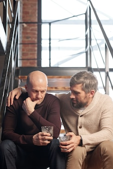 Middle-aged bearded man in cardigan sitting on stairs and giving advice to close friend while they drinking alcohol