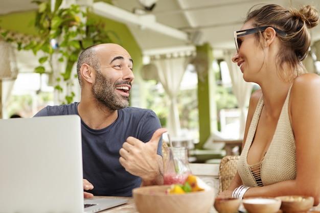 冗談を言いながらサングラスで彼のガールフレンドに親指を指している陽気な表情を持つ中年のひげを生やした男。