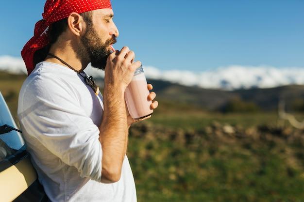 いちごの冷たいプレスジュースを飲む中年のクマの男