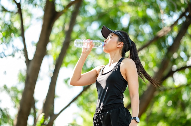 Middle-aged beautiful sport asian woman drinking water after jogging,healty and sport concept.