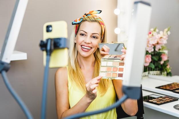 Красивая женщина средних лет и профессиональная красавица, визажист, влогер или блогер, записывают учебник по макияжу, чтобы поделиться им на веб-сайте или в социальных сетях.