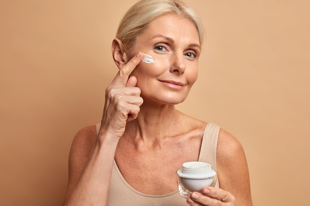 Middle aged beautiful woman applies anti aging cream on face undergoes beauty treatments cares about skin