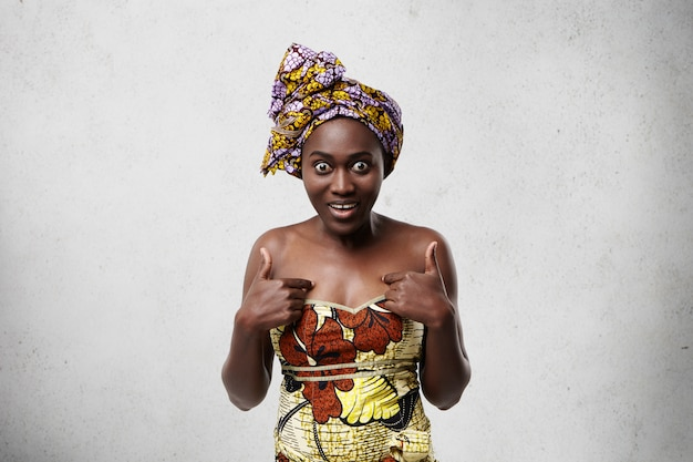 Middle-aged black woman in traditional clothes looking with widely opened eyes having surprised expression pointing at herself while posing against white concrete wall. shocked african model