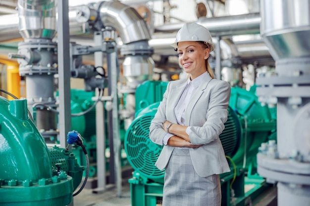 Middle-aged blond successful female ceo in suit with helmet on head standing in power plant with arms crossed