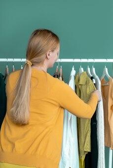 中年のブロンドの女性は買い物をし、服を着て棚の近くの新しい黄色のドレスを見ます