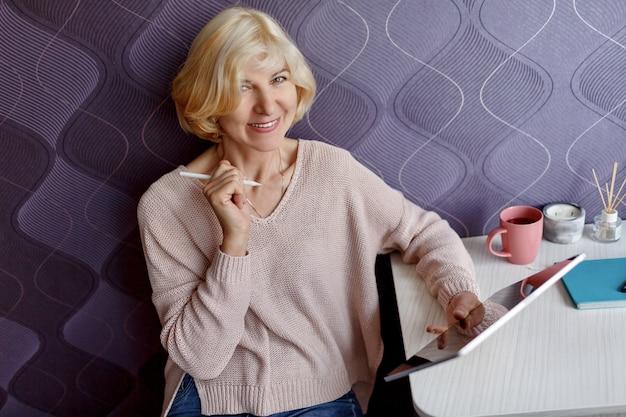 Среднего лет блондинка женщина с помощью планшета