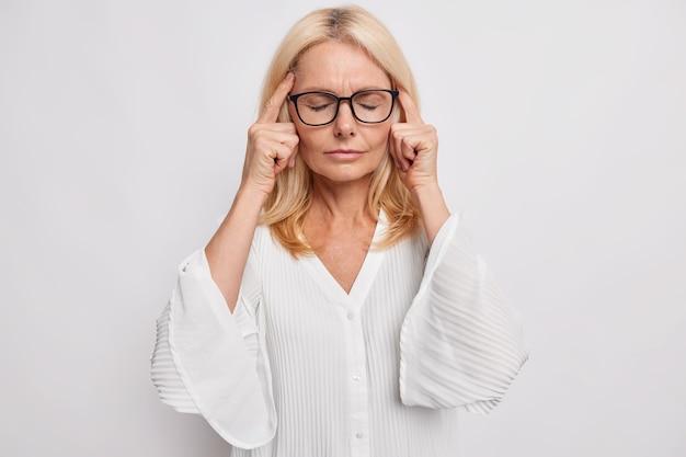 Блондинка средних лет привлекательная женщина держит пальцы на висках, страдает от головной боли, пытается вспомнить что-то важное, стоит с закрытыми глазами, носит очки, белая блузка сталкивается с серьезной проблемой