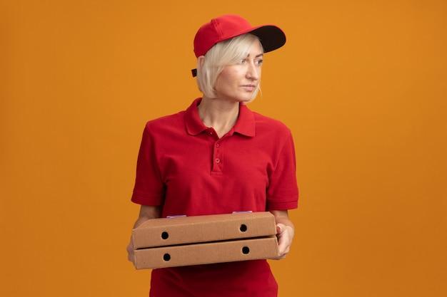 빨간 제복을 입은 중년 금발 배달부와 피자 패키지를 들고 있는 모자를 쓰고 복사 공간이 있는 주황색 벽에 고립된 쪽을 바라보고 있습니다.