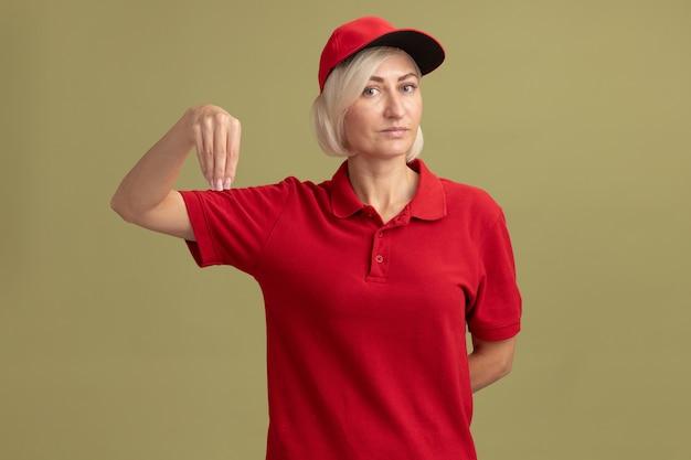 La donna bionda di mezza età delle consegne in uniforme rossa e berretto finge di tenere qualcosa tenendo la mano dietro la schiena