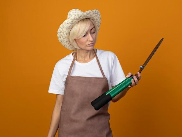 Светловолосая женщина-садовник средних лет в униформе в шляпе держит и смотрит на ножницы для живой изгороди, изолированные на оранжевой стене с копией пространства