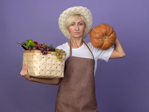 Светловолосая женщина-садовник средних лет в униформе в шляпе держит корзину с овощами и ореховой тыквой на плече