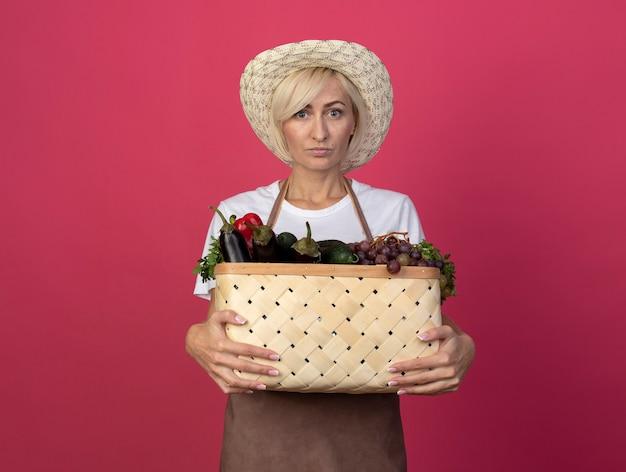 Светловолосая женщина-садовник средних лет в униформе в шляпе держит корзину с овощами, глядя вперед, изолированную на малиновой стене с копией пространства