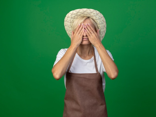 Middle-aged blonde gardener woman in uniform wearing hat covering eyes with hands isolated on green wall with copy space
