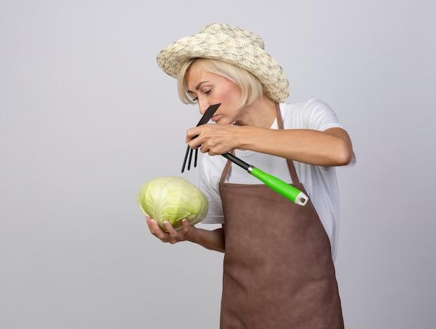 Donna bionda di mezza età del giardiniere in uniforme che indossa cappello che tiene cavolo e rastrello sopra di esso guardando cavolo isolato sul muro bianco con spazio di copia