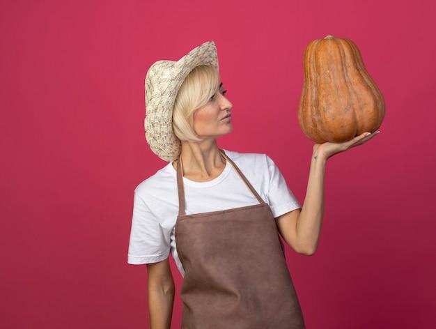 Donna bionda di mezza età del giardiniere in uniforme che indossa il cappello che tiene e che esamina la zucca butternut isolata sulla parete cremisi con lo spazio della copia