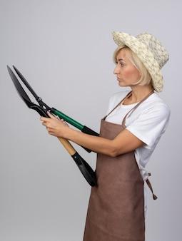 Donna bionda di mezza età del giardiniere in uniforme che indossa il cappello