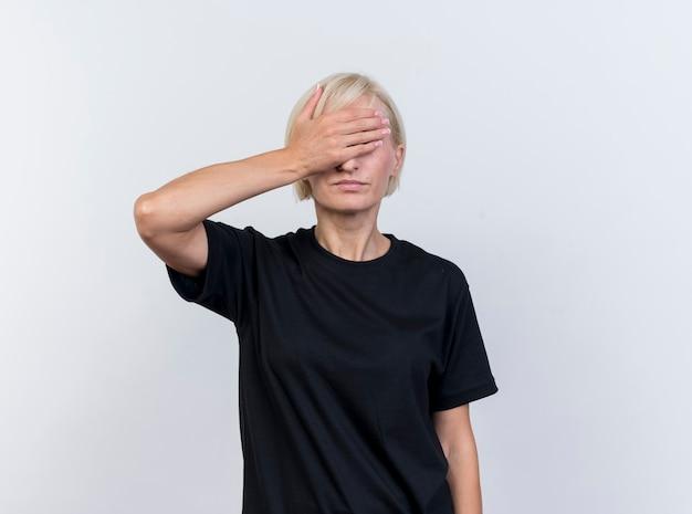 Donna slava bionda di mezza età che copre gli occhi con la mano isolata su sfondo bianco con spazio di copia