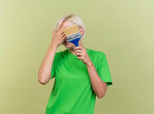 コピースペースのあるオリーブグリーンの壁に隔離された手で顔を覆う顔の前にペイントブラシを保持している中年の金髪のスラブ女性