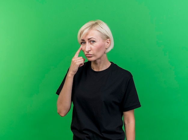복사 공간이 녹색 벽에 고립 된 눈 아래에 손가락을 넣어 앞을보고 중년 금발 슬라브 여자