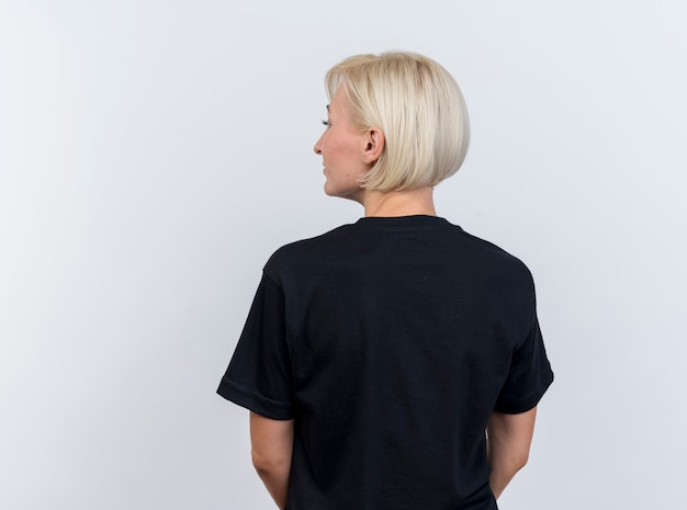 コピースペースで白い背景で隔離の側を見て後ろのビューに立っている中年の金髪のスラブ女性