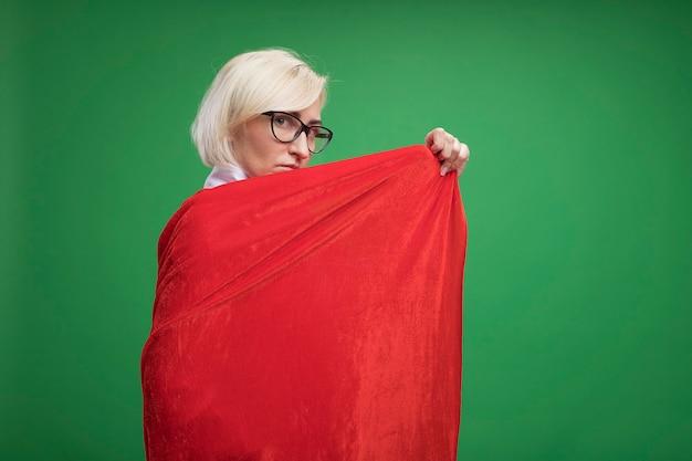 縦断ビューで立っている眼鏡をかけている赤いマントの中年の金髪のスーパーヒーローの女性は、後ろから正面を見てそれで自分自身を覆っている彼女のヒーローマントをつかんでいます
