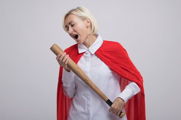 Middle-aged blonde superhero woman in red cape holding baseball bat using it as microphone singing with closed eyes isolated on white wall with copy space
