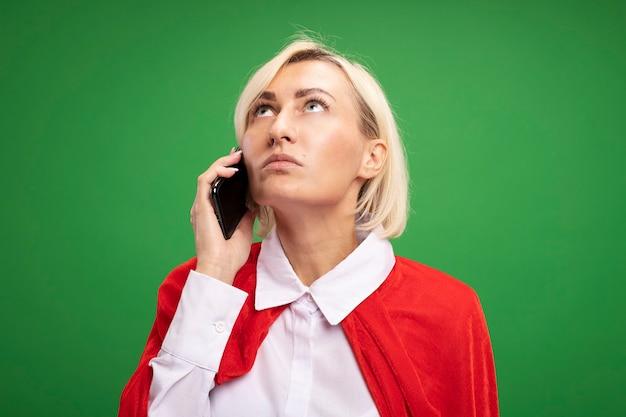 Donna bionda di mezza età del supereroe in mantello rosso che parla sul telefono che osserva in su isolato sulla parete verde