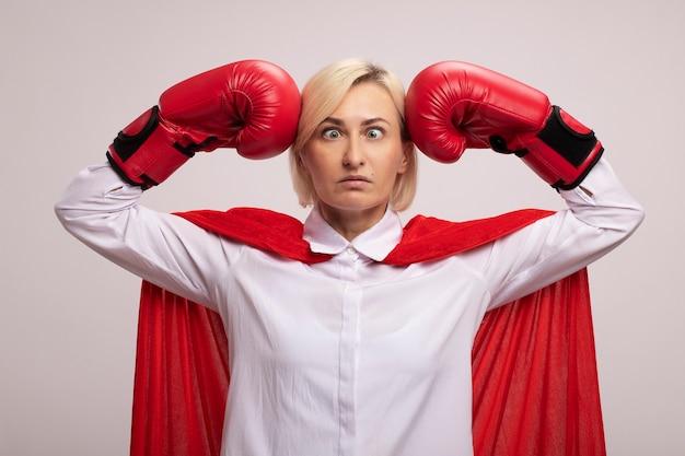 Donna bionda di mezza età del supereroe in mantello rosso che indossa i guanti della scatola che si batte in testa con gli occhi incrociati
