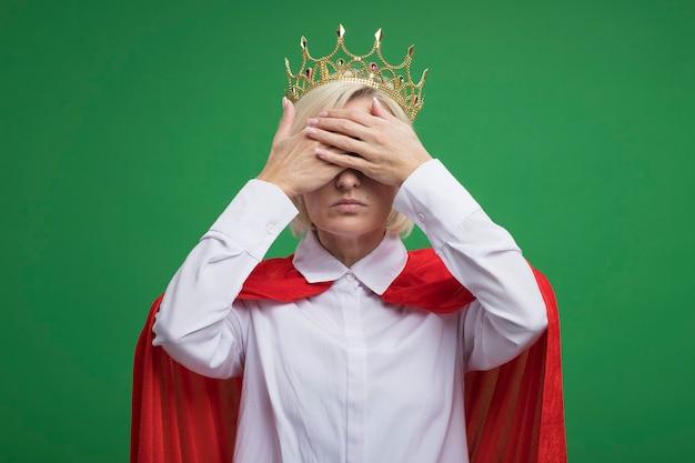 Donna bionda di mezza età del supereroe in mantello rosso con gli occhiali e la corona che copre gli occhi con le mani